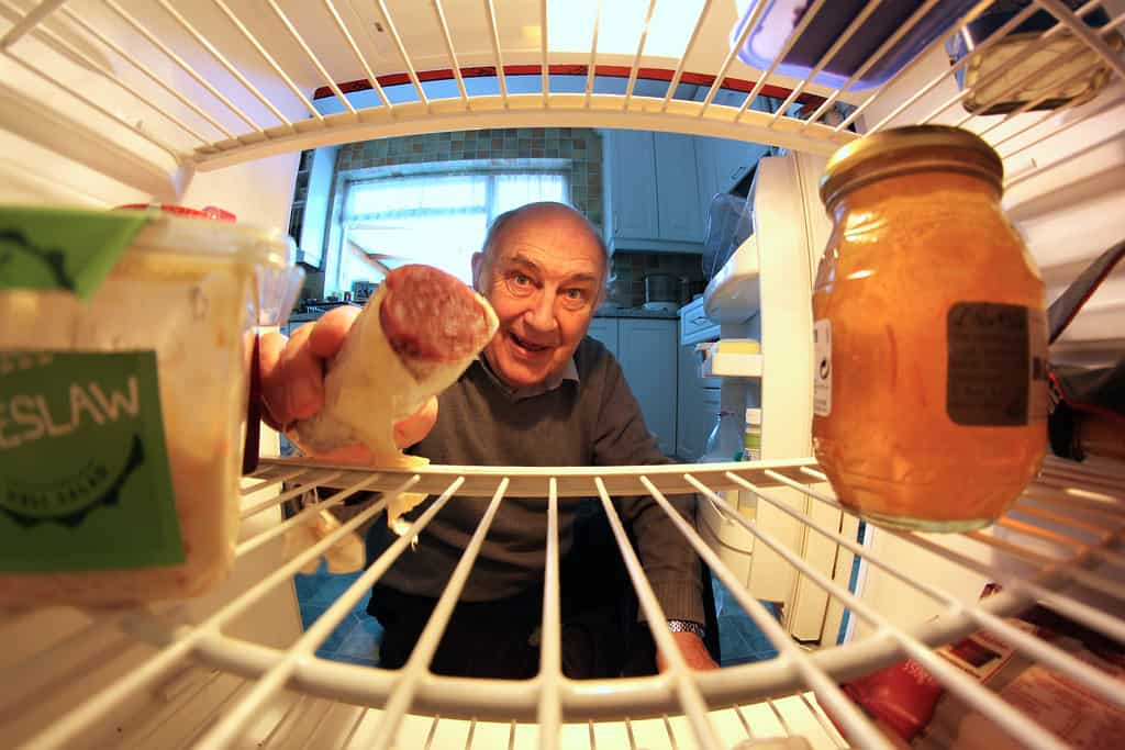man reaching into the refrigerator
