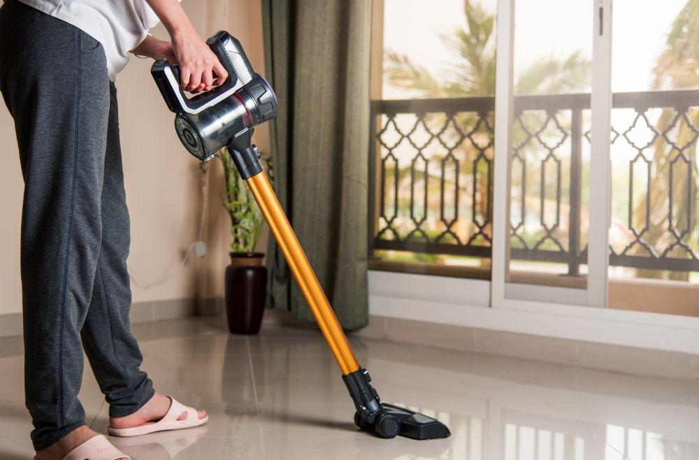 man cleaning using Stick vacuum