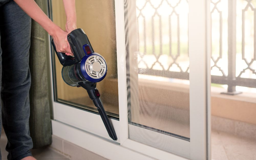 man cleaning window using stick vacuum