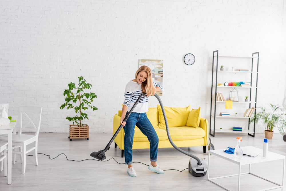 woman happily cleaning using corded vacuum