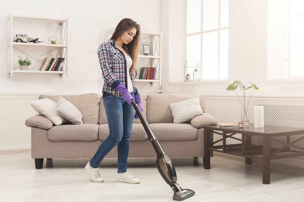 young mom cleaning using upright vacuum
