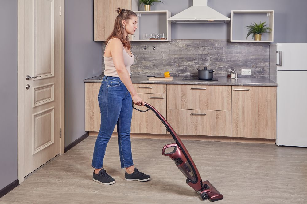 young woman cleaning using cordless vacuum